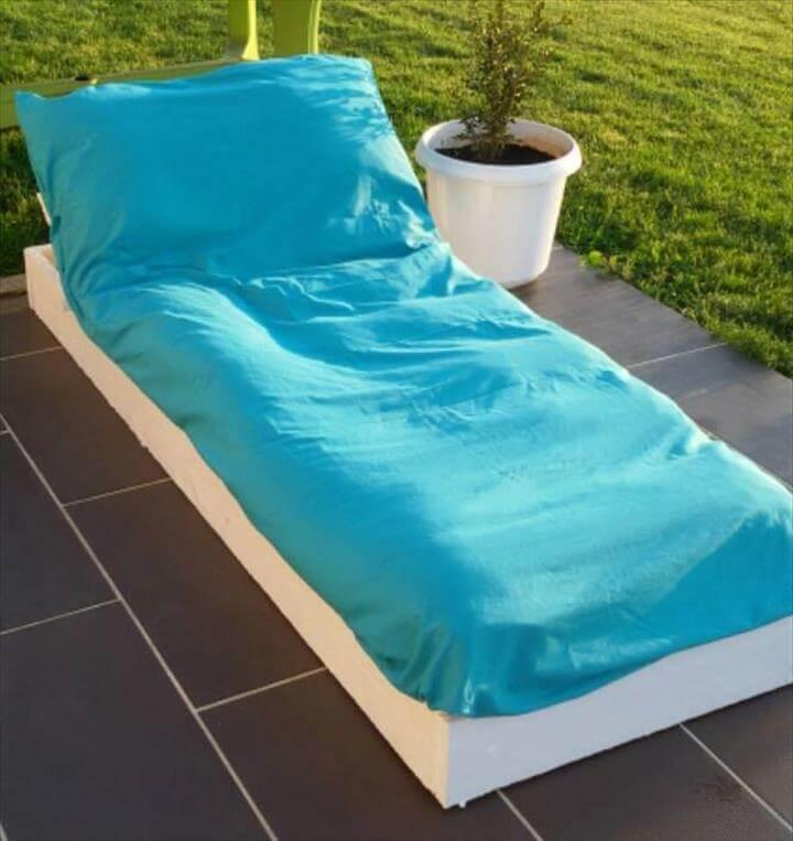 recycled pallet outdoor lounger with blue cushion
