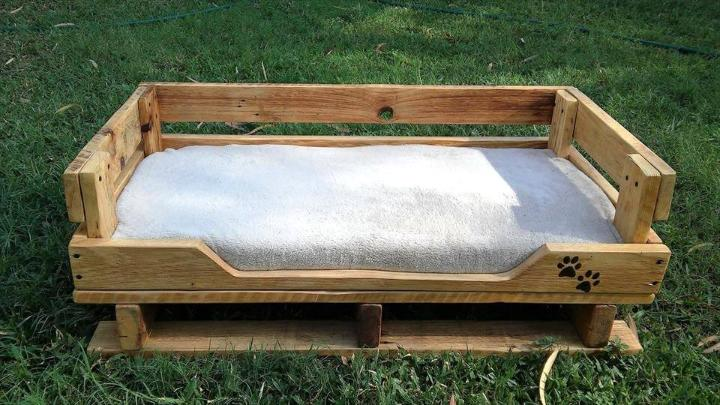repurposed wooden pallet dog bed with white cushion