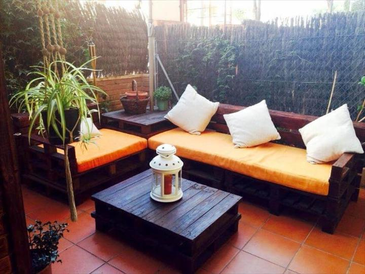 dark stained pallet L-shape sitting set with orange cushions