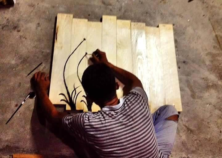 painting the dandelion flower over the pallet-made board
