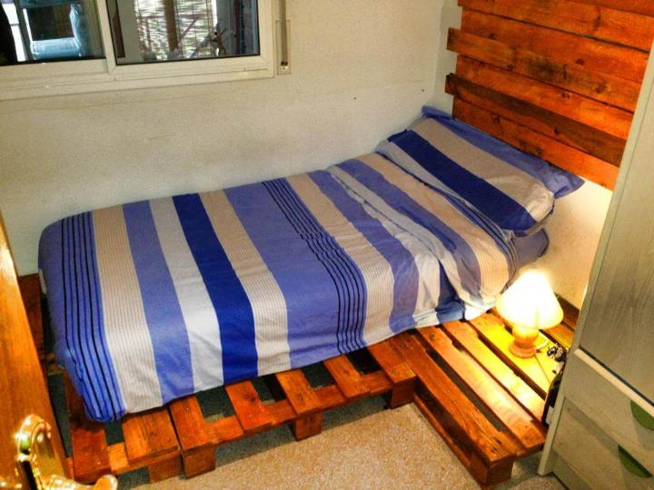 wooden pallet bed with nightstand and headboard wall