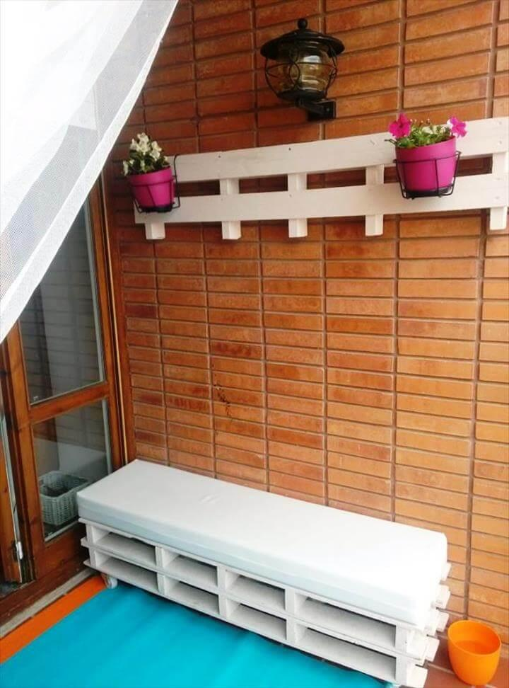 white painted stacked pallet bench and wall hanging pot holders