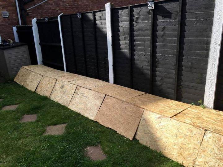 adding plywood pieces over stacked pallets